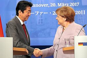 共同会見を終え、ドイツのメルケル首相(右)と握手する安倍晋三首相=20日午後1時58分、ドイツ・ハノーバー、林敏行撮影