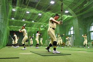 室内練習場で素振りをする創志学園の選手たち=阪神甲子園球場