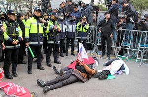 朴槿恵前大統領の自宅前で、朴氏の検察出頭を阻止しようと道路に寝そべる支持者ら=21日午前7時7分、ソウル、李聖鎮撮影