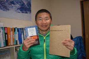 著書の『山の天気にだまされるな!』(左)を持つ猪熊隆之さん。右は西穂高岳落雷事故の報告書