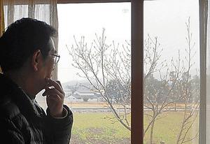 庭のモクレンの木を眺める山内悟さん=15日、福島県楢葉町