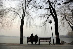 北京で池のほとりに腰掛ける高齢の男女=ロイター
