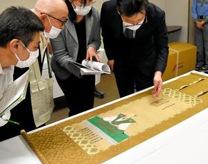 修理が終わった信長像を確認する学芸員ら=1日、豊田市陣中町1丁目の市郷土資料館