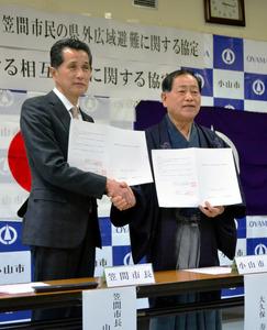 握手を交わす山口伸樹・笠間市長(左)と大久保寿夫・小山市長=小山市役所