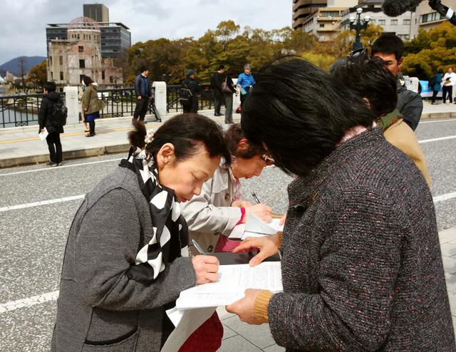 被爆者団体の呼びかけに署名をする人たち=21日午後、広島市中区、上田幸一撮影