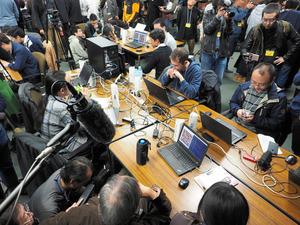 絶芸とZenの決勝戦(手前の向きあうパソコン2台)。大勢の報道陣とギャラリーに囲まれながら、開発者は対局の推移を見守った=19日午後3時14分、東京都調布市の電気通信大