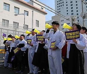 韓国・釜山の日本総領事館前で、慰安婦問題の日韓合意の無効などを訴えてデモ行進する人たち