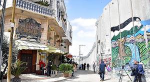 パレスチナ自治区ベツレヘムに開業したホテル(左)。目の前に分離壁がある=渡辺丘撮影