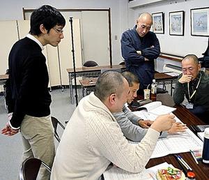 グループに分かれ、ケーススタディーに取り組む「未来の住職塾」の塾生たち。後ろから見守るのは松本紹圭(右)と井出悦郎の両講師