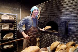 パンを手作りの石窯から取り出す田村陽至さん=金川雄策撮影
