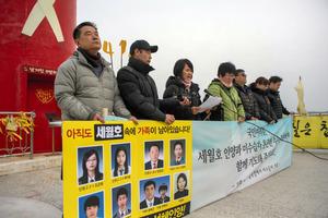 韓国南西部・珍島で22日、声明を発表する旅客船セウォル号沈没事故犠牲者の遺族。船体の引き揚げ作業が予定されている=AFP時事