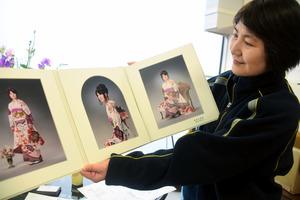 娘の彩さんの成人式の写真を見せる中島裕美子さん=糸魚川市上刈3丁目