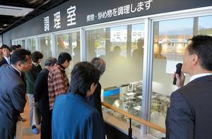 「食育のみち」から1階の調理室をのぞく完成式の参加者ら=富士宮市北山