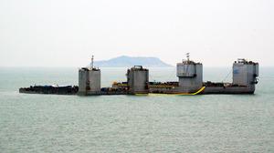 22日午前、珍島沖の事故現場海域で始まったセウォル号の船体引き揚げ試験作業(韓国海洋水産省提供)