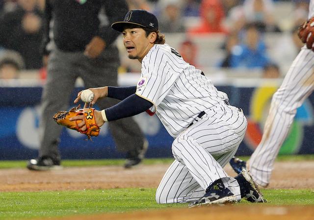 八回表アメリカ1死二、三塁、A・ジョーンズの打球をはじいた三塁手の松田(左)。右は遊撃手坂本勇=時事