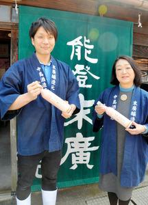 父が開発した桜色の日本酒「花おぼろ」を手にする蔵元杜氏の中島遼太郎さん(左)と母喜久子さん=輪島市鳳至町稲荷町