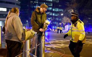 ロンドンで22日、事件が起きたウェストミンスター橋の現場付近に花束を供える人たち=ロイター