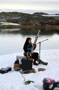 氷上でシタールを奏でるミュージシャン=21日、南極、板垣麻衣子撮影