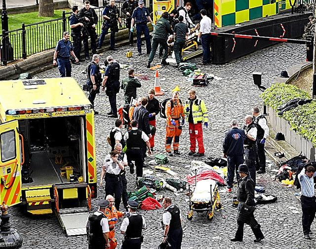 22日、ロンドンの国会議事堂付近で起きた事件の現場で救護活動にあたる救急隊員ら=AP