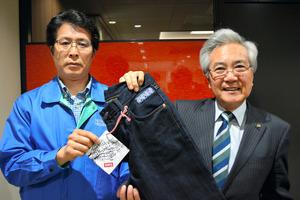 贈られたエドウインのジーンズを手にする葛西市長(右)と小野工場長=弘前市役所