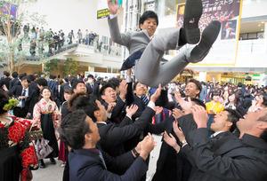 胴上げして卒業を互いに祝う学生たち=大分市のiichiko総合文化センター