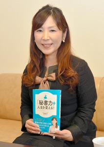 著書「『秘書力』で人生を変える!」を手にする田巻さん=鹿児島市