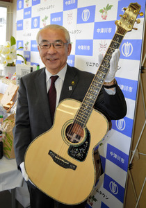 「ふるさと納税」の返礼品になった高級ギターを持つ青山節児市長=中津川市役所
