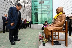 22日午後、釜山総領事館前に設置された慰安婦問題を象徴する少女像に頭を下げる洪準杓・慶尚南道知事=洪氏選挙対策事務所提供