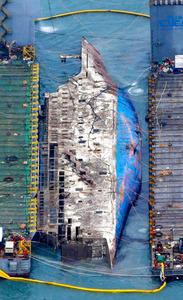 23日、引き揚げられるセウォル号の船体=ロイター