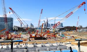 公開された新国立競技場の建設現場。大型のクレーンの向こうに東京体育館や新宿のビル群が見える=24日午前、東京都新宿区、嶋田達也撮影