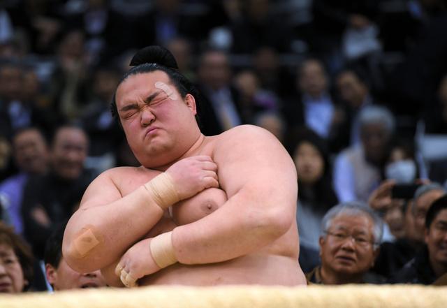 日馬富士に寄り倒しで敗れ、土俵下で左の肩に手を当てて顔をしかめる稀勢の里=伊藤進之介撮影