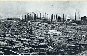 本土初の空襲を受けた翌日の1944年6月17日に撮影されたとみられる八幡市街地。奥に並ぶ煙突は八幡製鉄所=米国立公文書館所蔵