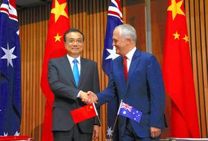 オーストラリアの首都キャンベラで24日、署名式を前にターンブル豪首相(右)と握手する李克強首相=ロイター