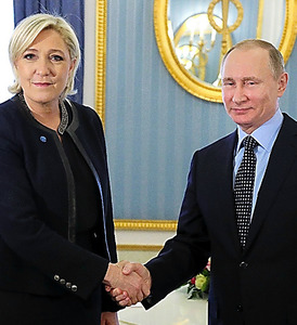 モスクワのクレムリンで24日、握手するロシアのプーチン大統領(右)とフランスの右翼・国民戦線のルペン党首=AFP時事