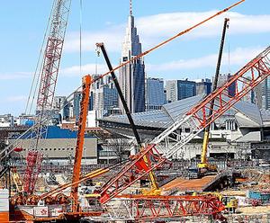 新国立競技場の建設現場。大型のクレーンの向こうに東京体育館や新宿のビル群が見える=24日午前、東京都新宿区