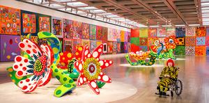 天井高5メートル、奥行き50メートルほどの展示室に並ぶ連作「わが永遠の魂」。今も描き続けて500点を超える中から、132点を厳選した。花の彫刻も置かれた鮮やかな大空間に満足げな草間さん。