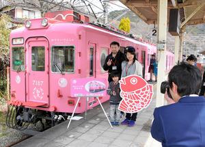 「めでたいでんしゃ」の前で記念撮影をする親子連れ=和歌山市加太