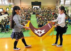 返納する校旗を丁寧に畳む児童代表ら=大分市中島西2丁目