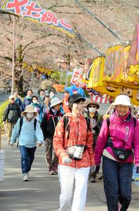 桜が咲き始めた大宮公園を歩く参加者たち=さいたま市大宮区