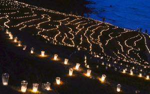 約3万本のろうそくで暗闇に浮かび上がる白米千枚田=25日午後6時45分、石川県輪島市、板倉吉延撮影