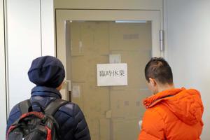 発券を巡るトラブルを起こした旅行会社「てるみくらぶ」の本社があるビルには利用者が集まった。会社の扉には「臨時休業」と書かれた紙が張られていた=25日午後、東京都渋谷区