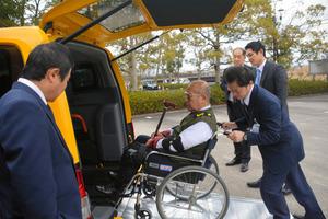 スロープ付きのタクシーに車いすを押して入れる受講者=守山市木浜町