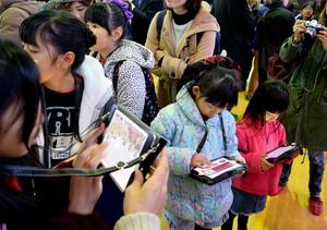 イベントでタブレット端末の画面に見入る子どもたち=西東京市