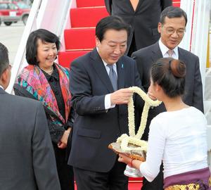 政府専用機でカンボジア・プノンペン国際空港に降り立ち歓迎を受ける野田佳彦首相(中央)と仁実夫人(左)=2012年11月