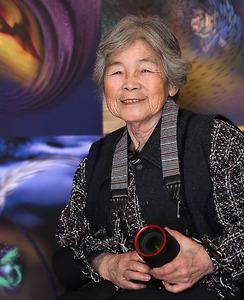 自身が創作したデジタルアートの作品を背景に、カメラを持つ西本喜美子さん=熊本市東区、河合真人撮影