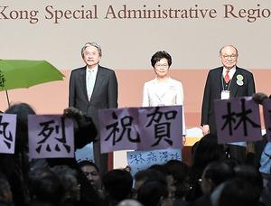 林鄭月娥氏(中)の当選発表後、雨傘を持った人が抗議する一方、「熱烈祝賀」と書かれた紙を持って当選を歓迎する人も=26日、香港の香港会議展覧センター、益満雄一郎撮影