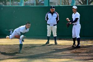 投球練習に取り組む投手陣と大須賀康浩監督(中央)=兵庫県西宮市