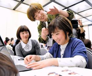 ヘアドネーションを学ぶイベントで、ウィッグの試着体験をする女の子=27日午後、大阪市北区、遠藤真梨撮影