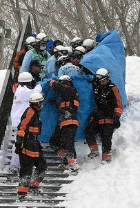 雪崩から救出された人を搬送する消防隊員ら=27日午後2時26分、栃木県那須町、恵原弘太郎撮影