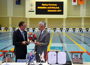 オーストラリア水泳連盟のマーク・アンダーソンCEOに手まりを渡す長岡市の磯田達伸市長(右)=28日、長岡市のダイエープロビスフェニックスプール